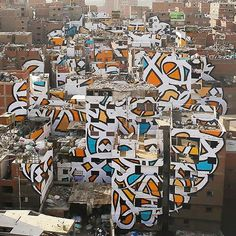 'calligraffiti' artist @eLSeed challenges cultural perceptions with city-scale anamorphic #art in #cairo. the piece spans across 50 buildings in the community of zaraeeb and is only completely visible from a specific point on the mokattam mountain.  read the full article on #designboom.com/art/