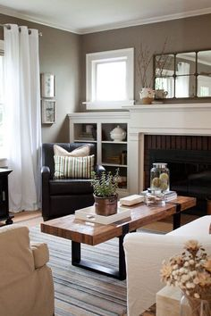 Light fireplace with darker wall, white trim, white built in shelves, neutral furniture, blue and dark brown accents