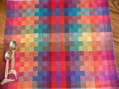 Hand woven tea towel designed and woven with a rainbow of bright multiple colors on a background of rainbow hues in a fancy twill weaving pattern using 100 percent cotlin yarn. Cotlin yarn has been spun with 60 percent linen and 40 percent cotton creating a strong yet soft to the touch yarn.  This textile is soft and absorbent and yet very sturdy and long wearing. Each towel measures approx. 17 wide x 30 long and has machine sewn hems.  Handwoven towels are perfect for those of us who aspire…