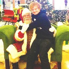 Ed Sheeran sitting on Santa's lap.