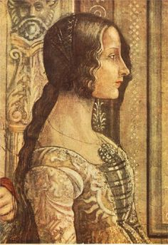 Uncovered hair with two tresses on either side of the face, the rest pulled back, typical of Italian Renaissance style. Low, rounded neckline with laces across the center, beneath which could be the camicia.