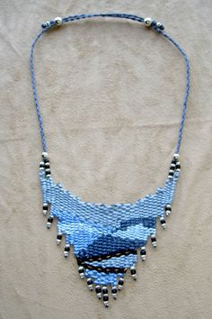 """""""Blue Ridge Parkway"""" - 2010 - Inspired by a trip to the Blue Ridge Parkway, showing the blue mountain range and small divided highway traveling through the mountains.  Adjustable length with sterling silver beads and slider beads.  PRIVATE COLLECTION.  Woven by Terri Scache Harris, theravenscache.shutterfly.com   Hand woven, handwoven, weaving, weave, needleweaving, pin weaving, woven necklace, fashion necklace, wearable art,  fiber art."""