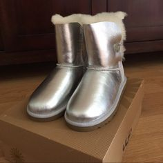 Silver UGG boots New with box, these cute boots have a button detail on the side of each shoe that's not only fashionable but functional too. UGG australia Shoes Winter & Rain Boots