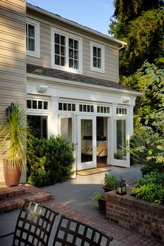 Pretty, traditional porch with brick accents and multiple levels. Like the French doors and transoms.