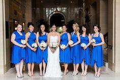 Bride in strapless lace wedding dress and bridesmaids in cobalt blue bridesmaid dresses