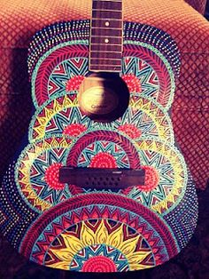 Painted guitar art byJamie Mcalpin with red lotus and henna designs.
