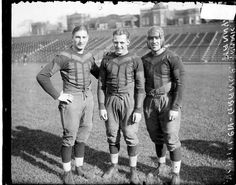 "[Chicago Bears football players Harold ""Red"" Grange, Frank Hanny, and McMillen standing on the field at Weeghman Field 1925."