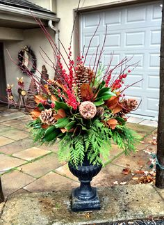 Luxurious Christmas urn arrangement of magnolia leaves, hypericum berries, sugar comes, cedar boughs and dogwood branches.  By Caruso & Company