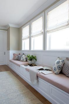 A cream colored rug sits in front of a long built-in white window seat fitted with drawers and blush pink linen cushions flanking a built in table fixed against a wainscot backsplash beneath three windows dressed in natural linen roman shades complementing tan upper walls.