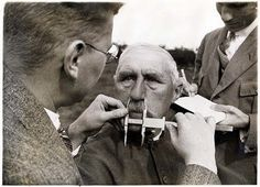 A man is having his nose measured by the Nazi police police to decide whether or not he is Jew. Hitler had a stereotype that Jewish noses are larger than Aryan noses.