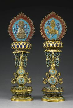 A PAIR OF CHAMPLEVE ENAMEL ALTAR ORNAMENTS QING DYNASTY, 18TH / 19TH CENTURY each with a flaming mandorla applied on either side with relief decoration, one with a horse supporting a vase of precious objects on its back, the other with a seated queen, all atop a lotus pod raised on three champléve foliate scrolls, issuing from a beribboned double-gourd vase decorated with the characters da and ji, the lobed base divided in the middle by an openwork panel of conforming shape