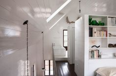 Skylights, white reflective paint enables sharing of light from attic to downstairs.  Rustic Bedroom by Jean Longpré