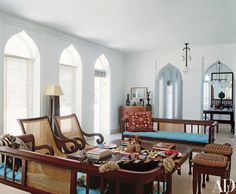 In the living room, benches and chairs Al-Harthy Sheridan designed are grouped around an overscale low table topped with books, artifacts and Iznik ceramics. The narrow, pointed-arch windows are typical of Omani architecture and help cool the space. The designer wanted an eclectic interior and culled inspiration from around the world. A Swedish motif, which she embroidered herself, adorns a settee pillow.