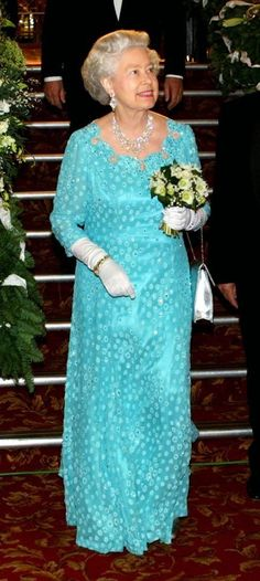 2001: At a Royal Variety Performance two years later, the Queen opts for a block turquoise colour dress with white gloves and a silver handbag