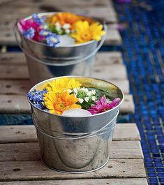 Decoração rústica com flores e velas em vasinhos de metal.