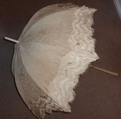 a very fine quality 19th century parasol. The cover is made of three rows of silk fringes towards the edge of the cover and the rest of the parasol is covered with Brussels lace. The ivory handle is carved and embellished with gold coloured metal inserted with many turquoise and coral cabochon. The maker is Brigg & Sons, London