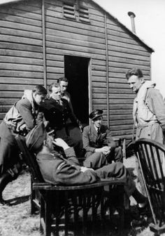 Pilots of No. 303 Fighter Squadron rest in front of a dispersal hut at RAF Northolt in September 1940. From left are: Pilot Officer Witold 'Tolo' Lokuciewski (leaning on the chair); Flight Lieutenant Witold Urbanowicz (seated in the chair in the foreground); Zygmunt Wodecki, the squadron doctor (in a dark uniform); Sergeant Josef Frantisek (in the back, face partially covered); Flight Lieutenant John Kent; Flying Officer Ludwik Paszkiewicz. HU 106457.