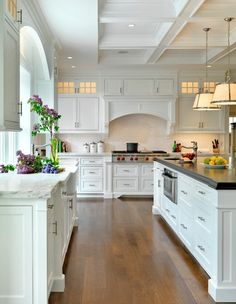 Style: traditional Category: kitchen Keywords: archway · black countertop · coffered ceiling · cooktop · drum pendant light · glass cabinet · kitchen island sink · marble countertop · stainless steel · under-cabinet lighting · white cabinets · white ceiling · white kitchen · white tile backsplash · white wall · wood floor