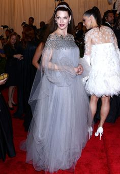 #LindaEvangelista con un #look de #vestido gris perla de tul, tiara y #maquillaje muy blanquecino y labios color cereza.