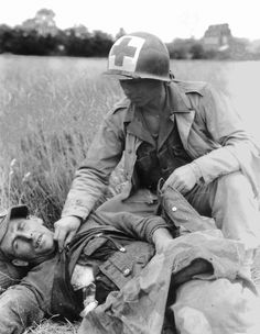 Medic Cpl. Roy C. Moore examining a wounded German prisoner in a field near the French town of Countances, 1944