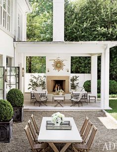 Sofas by Janus et Cie and 1950s French woven chairs from the Nicholson Gallery beckon from the terrace; the sunburst mirror is vintage | archdigest.com