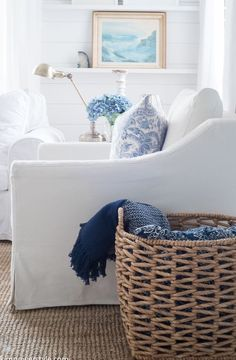 Blue and white decor with modern coastal nautical feel thanks to woven storage baskets and beachy art