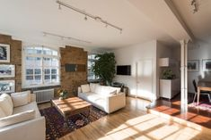 brick-walls-white-sofas-plants-and-wooden-floor