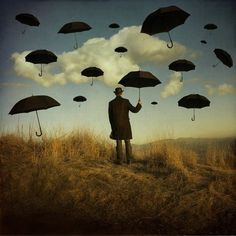 Man holding a black umbrella with black umbrellas in the  sky art
