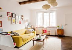 This is a lovely livingroom - light, wood, white & yellow + artwork and colourful pillows.
