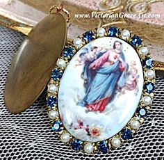 $89 Vintage porcelain cameo locket pendant featuring the Blessed Mother Virgin Mary as The Sacred Immaculate Heart surrounded by angels & cherubs. Deep medium blue rhinestones and white pearls.  The locket can hold 2 photo's or prayer petition requests to the Holy Mother.