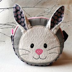 Taštička králíček Taštičkaušitá z bavlny a syntetiky.Vše je podlepenéronofixem pro pevnější tvar.Aplikace podlepená vlizelínem a strjově přišité.Popruh nastavitelný.Možnost šetrného praní na 30C°  Výška:15cm šíře:16cm Michael Miller Fabrics USA