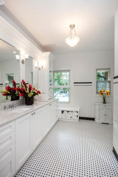 This pristine, newly remodeled master bathroom features clean lines for easy living. Designed by TriplePoint Design Build, the room displays a bright white backdrop with two black accent stripes on the walls and a black and white basketweave mosaic tile floor to provide dimension and contrast. The look is classic and sophisticated.