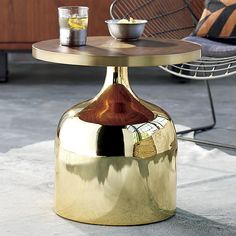 Bousaf Side Table / Natural and glam elements live harmoniously in this sculptural design. The shiny brass-plated metal base gleams in one continuous contour, topping out with a round of walnut veneer inset with a metallic center for a concentric aerial view.