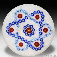 """Parabelle Glass 1988 interlaced garland millefiori paperweight. Two interlocking garlands of light blue and dark blue complex canes surround a central red millefiori cane encircled by eight smaller blue complex canes with yellow centers on an upset muslin ground; each loop of the garlands contains a red millefiori cane. Signature/date cane. Diameter 3 1/4"""". www.theglassgallery.com"""
