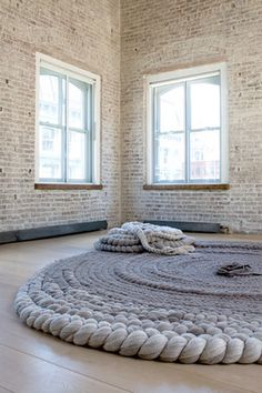 The rope/carpet/art installation looks like the perfect carpet/decoration piece for a living room in a house with brick walls.