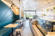 In this modern cafe, a long L-shaped service counter kinks and bends along its length, and the floor is made from concrete resin as it's a practical and hard-wearing material.