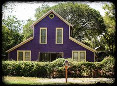 """An old pull-through (tractor) barn in New Braunfels, Texas, has been converted into a lovely home, complete with a spiffy purple paint job, on the barn house and the garage on the right."""