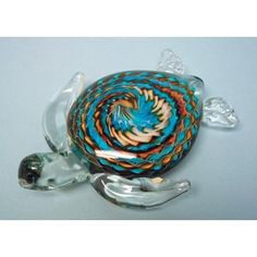 "This gorgeous turtle has a clear head and fins with swirling colors of turquoise blues creamy beige-browns and hints of green on its back. 8"" long"