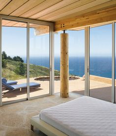 Two walls of floor-to-ceiling windows in the master bedroom frame expansive vistas of the Pacific Ocean.  Photo by Robert Canfield.