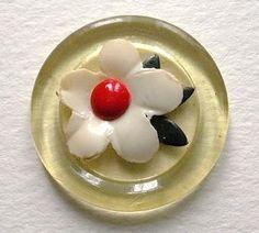 Bouton celluloid Vintage, translucide jaune avec une fleur sur pellicule blanche appliquée & feuilles, très délicats. C1930.