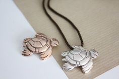 """Sea turtle jewelry- """"Tortuguita"""". 2011 Good luck charm, silver 925°, also available pink-gold plated, by Liana Vourakis. Size: 3 cm. Inspired by a traditional Mayan design, found in Belize, Central America. """"Tortuguita"""" symbolises longevity, wealth and good fortune. It comes complete with cordon in the jeweler's handsome presentation bag."""