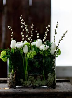 ♥ the deep emerald glass filled with snow white florals ... and the movement of the arrangement.