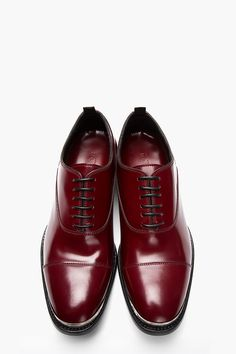 ALEXANDER MCQUEEN //  Burgundy red leather metal-trimmed shoes  32259M049003  Low-top buffed leather shoes in burgundy red. Round cap toe trimmed in silver-tone etched metal at foxing. Tonal oxford-style lace up closure. Pull tabs at collar. Tonal stitching. Black leather sole. Upper, lining, sole: leather. Made in Italy.  $815 CAD