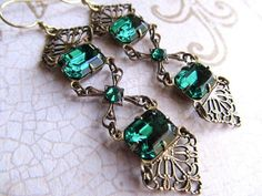 These art deco inspired earrings have rich emerald green crystal jewels. Combined with delicate filigree as well as an art deco piece in the center. The ear wires are brass and are naturally nickel and lead free. These easy to wear earrings are light on your ears. Feel rich in Luxurious!  *They measure from the top of the ear wires 3 or 74mm. *Nickel and lead free  *Here are more green earrings- https://www.etsy.com/listing/460733804/emerald-green-gothic-earrings-rhin...