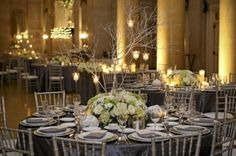 silver-table-linens-chivari-chairs: SILVER CLOTH, NAPKINS, WHITE AND GREEN FLOWERS WITH BRNCHES; SILVER CHIVARRIES WITH WHITE CUSHIONS. HOW ABOUT PURPLE NAPKINS JUST FOR HEAD TABLE?