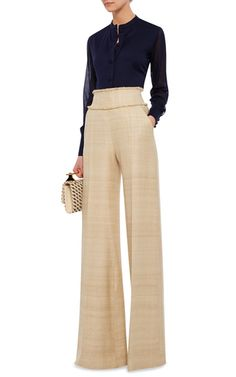 This **Martin Grant** trouser features a high rise with fringed trim at the waistband, slip pockets at the hips, and a wide leg silhoeutte rendered in a silk tweed.