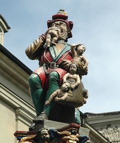 """What Makes It Strange: Though it sounds like an outlandish piece of modern art, the Kindlifresser, or """"Child Eater"""" fountain, has scared the children of Bern since 1546. Dressed in vibrant red and green robes, the rotund Kindlifresser is munching on an infant's head, while more distraught babies await their grim fate in his knapsack. Some postulate that the statue served as a warning to Bern's Jewish community, because the cannibal's hat resembles the yellow pointed version Jews were forced…"""