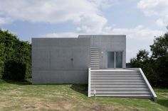 Two concrete cubes intersect to form the body of this house, which stands on a matching concrete platform.