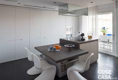 A parete e al centro: un po' a vista, un po' mimetizzata dietro i pannelli continui dell'armadiatura a tutta altezza, la cucina si compone di una parete attrezzata e di un'isola multifunzionale con la zona cottura e il tavolo da pranzo ad altezze differenziate; sotto i piani di entrambi gli elementi c'è posto per vani contenitori. L'area conviviale prosegue anche all'aperto, sul terrazzo.