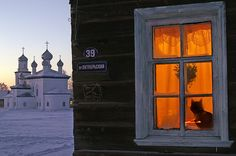 Snowy Russian church with a cat in the window, unknown source